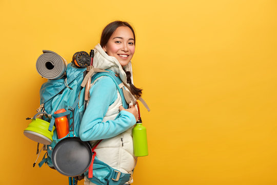 Positive Asian female hiker stands sideways to camera, carries big rucksack with necessary things for travel, has exciting adventurous trip, isolated over yellow wall, blank space on right side.