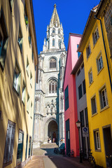 Fototapete - Old narrow street overlooking Konstanz Minster or Cathedral of Constance, Germany. It is landmark of old town of Constance. Scenery of medieval Gothic church in summer. Vintage alley in European city.