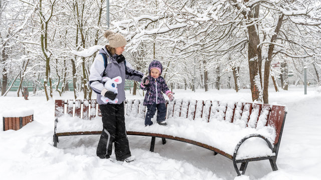 Family walks during snowfall in Moscow, Russia. Baby girl with mother are in winter park. Little child walks on snowbound bench by the mom's hand. Young woman and her kid play with snow outdoor.