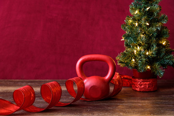 Christmas fitness, red kettle bell, with artificial Christmas tree and white lights, red ribbon, wood table, red background