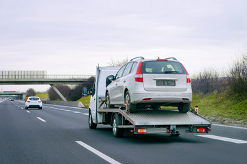 Tow truck with car on warranty on road. Trailer and crash auto delivery. Vehicles hauler on driveway. European transport logistics. Heavy haul trailer with driver on highway.
