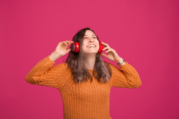 Photo of cheerful young woman, enjoying listening music at headphones, standing over pink background