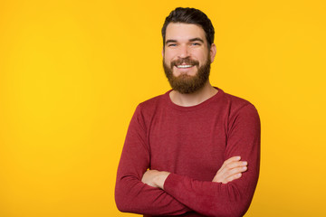 Photo of bearded guy, standing with crossed arms, looking and smiling at camera  over yellow isolated background