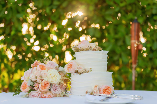 wedding cake and bridal bouquet on table