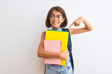Beautiful student child girl wearing backpack glasses books over isolated white background very happy pointing with hand and finger