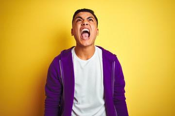 Young brazilian man wearing purple sweatshirt standing over isolated yellow background angry and...