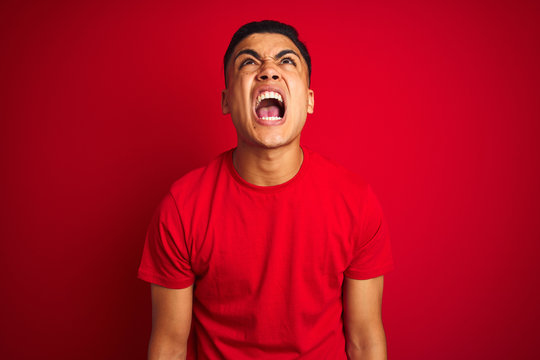 Young brazilian man wearing t-shirt standing over isolated red background angry and mad screaming frustrated and furious, shouting with anger. Rage and aggressive concept.