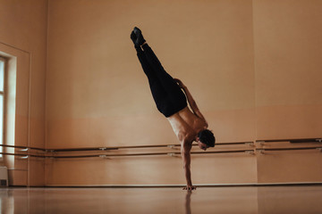 Rear view of male ballet dancer practicing one arm handstand.