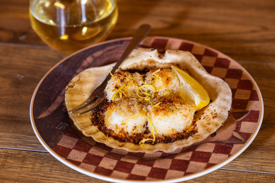 Four scallops baked on a scallop shell with breadcrumbs, lemon rind and butter, served on a plate, with a stemless wineglass of white wine, against a wood background.