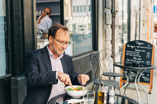 Businessman having lunch on a terrace in outdoor cafe, wearing a suit. Healthy green salad with salmon