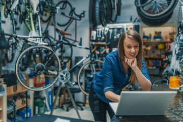 Creativity is a process. Woman mechanic working on a laptop. Female Bicycle Mechanic. Female mechanic in bicycle store. Young female mechanic with laptop