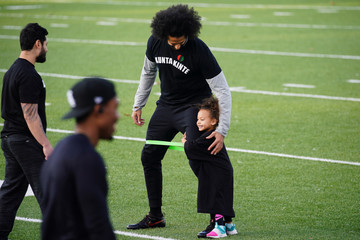 A girl hugs the leg of Kaepernick at a special training event at Charles. R. Drew High School in Riverdale