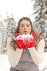 Beautiful, happy, healthy young woman having fun blowing snow from her hands. People enjoying playing outdoors in winter.