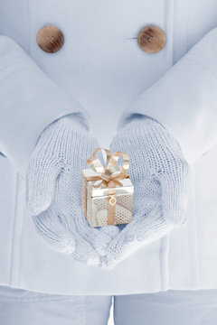 Close-up of woman's hands holding a special, fancy gold Christmas present. Luxury holiday gift giving background concept.