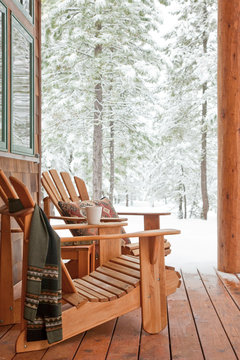 Adirondack chairs on porch of winter vacation home cabin with snowy forest landscape in background. Comfortable, rustic, relaxing winter getaway.