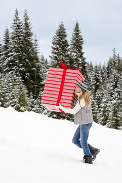 Beautiful, happy, smiling young woman holding carrying giant Christmas present in snowy landscape. Fun holiday gift giving concepts.