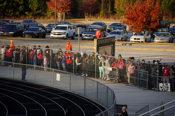 People watch through a fence as Kaepernick practices at a special training event at Charles. R. Drew High School in Riverdale