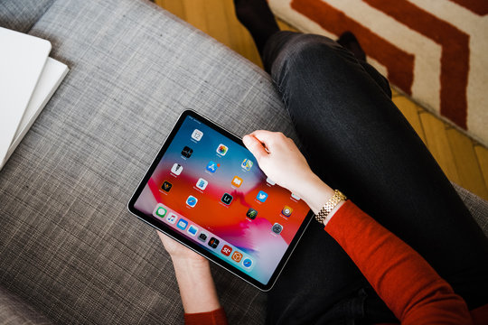 Paris, France - Feb 12, 2019: Overhead view of elegant woman holding new iPad pro tablet by Apple Computers on the couch in living room looking at home screen apps