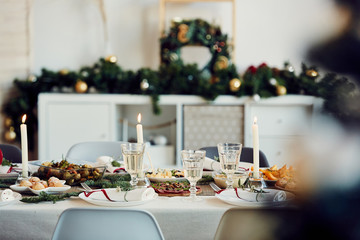 Background image of beautiful table setting for Christmas party with fir elegant candles and delicious homemade food, copy space
