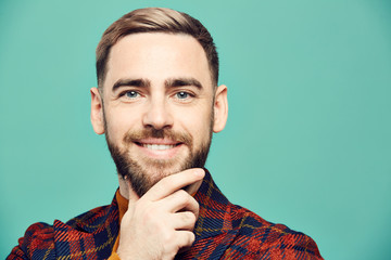 Head and shoulders portrait of smiling bearded man looking at camera while posing against mint green background, copy space