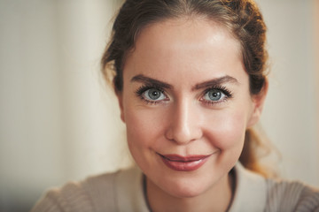 Close up portrait of beautiful adult woman smiling at camera while posing in home interior, copy space