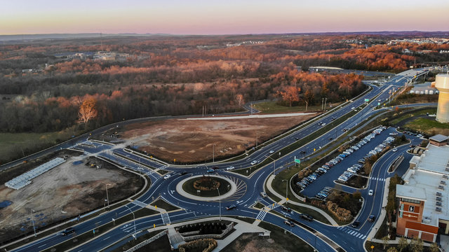 A traffic circle allows people to exit the highway to enter a parking lot.