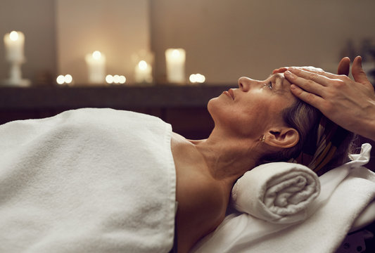 Side view portrait of elegant senior woman enjoying facial massage at luxury SPA center, copy space