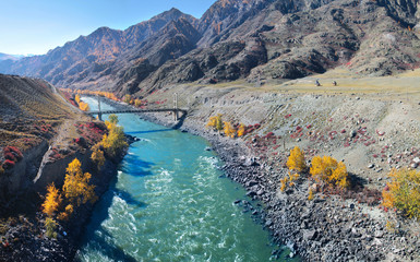 Wall Mural - The bridge across the Katun rivers in the Altai mountains. Sunny autumn day.
