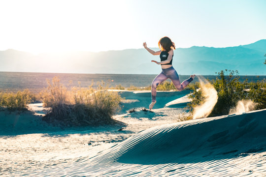Girl in yoga pants jumping off sand dunes