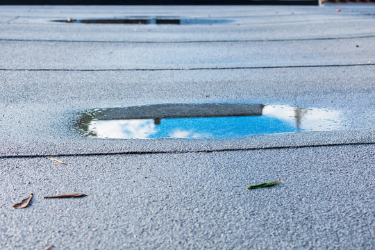Ponding rainwater on flat roof after rain is result of drainage problem. Roof leaking, settling, sagging, framing issues, rotten or saturated sheathing.
