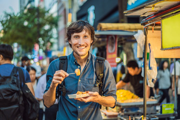 Fotobehang Seoel Young man tourist eating Typical Korean street food on a walking street of Seoul. Spicy fast food simply found at local Korean martket, Soul Korea