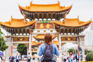 Back side of asian backpacker woman looking and sightseeing when travelling over the Jinbi square, Kunming, China, travel and tourism, china culture and traditional, famous place and landmark concept