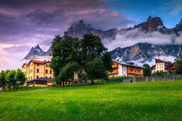 Wall Mural - Village with houses and high mountains at sunset, Dolomites, Italy