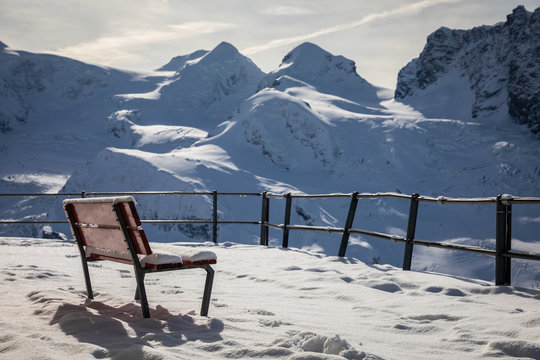 Bench covered by snow on terrace to watch snowcapped mountains