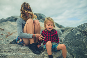 Young mother and toddler sitting on rocks