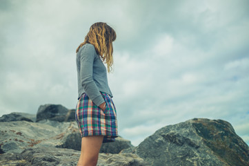 Young woman standing on some rocks against a cloudy sky