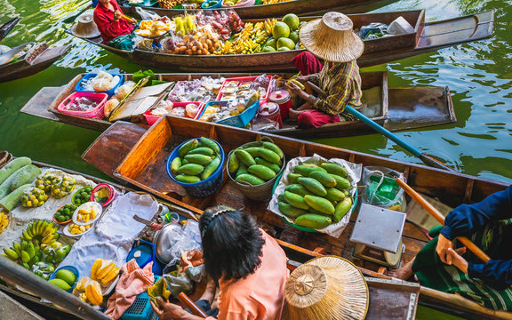 Top view Damnoen Saduak business floating market, Fruit food on Thai tradition boat in canal, Popular famous landmark water tourist travel Bangkok Thailand, Tourism beautiful destinations place Asia