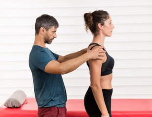 Male osteopath doing a postural evaluation