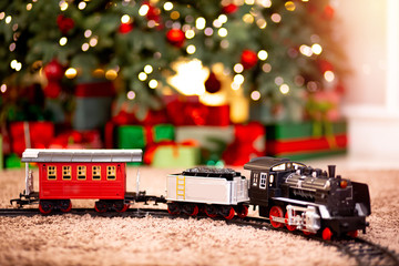 Christmas toy train in background illumination and New Year tree