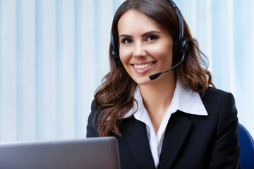 Portrait of young customer support female phone operator or sales agent in headset and confident black suit, working with laptop at office workplace. Consulting and assistance service call center.
