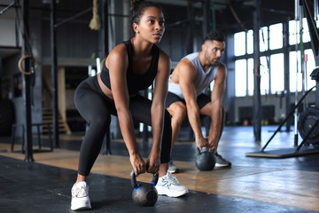 Deurstickers Fitness Fit and muscular couple focused on lifting a dumbbell during an exercise class in a gym.