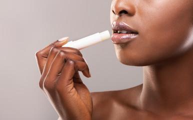 Fototapete - African american woman applying hygienic lip balm