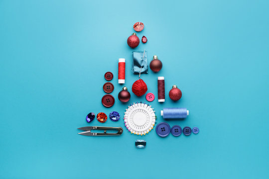 Beautiful Christmas tree made of sewing supplies on color background