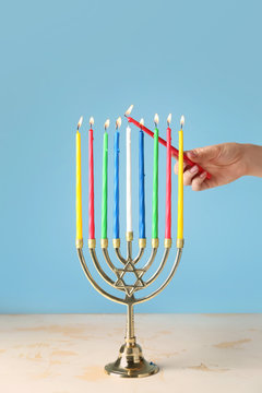 Woman lighting candles in menorah for Hanukkah on color background