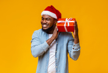 Happy african guy shaking Christmas gift box, listening what rattles