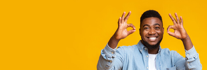 Positive black man gesturing ok sign with both hands Wall mural