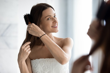 Happy attractive young woman brushing long hair looking in mirror