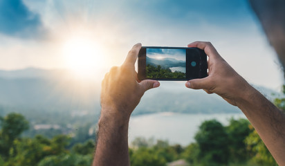 Smartphone hands shooting a beautiful landscape with sunset, travel concept and photography