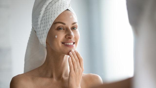 Smiling beautiful lady apply skincare cream look in mirror