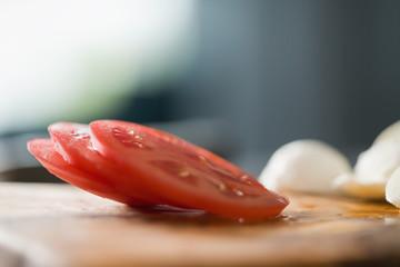 Fototapeta Closeup sliced red tomato on olive board obraz